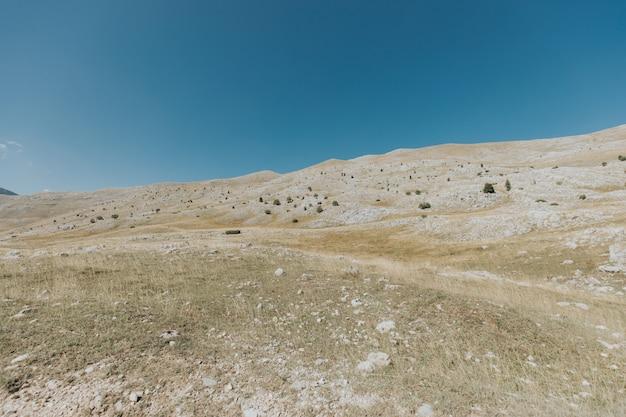 Вертикальный снимок гор и холмов с множеством камней под красивым голубым небом Бесплатные Фотографии