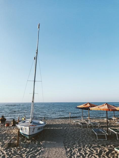 青い空と水の近くの海岸に白いヨットの垂直ショット、 無料写真