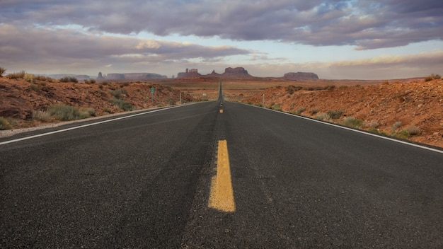 Горизонтальный снимок пустой дороги в долине монументов, сша на фоне захватывающего дух неба Бесплатные Фотографии