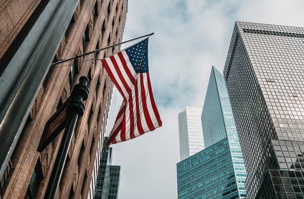 Флаг сша или соединенных штатов америки на флагштоке возле небоскребов под облачным небом Бесплатные Фотографии