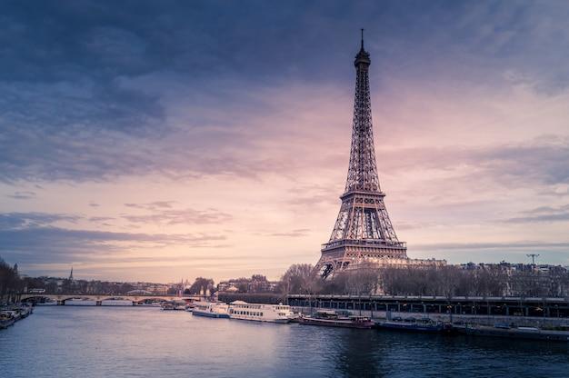 Красивый широкий снимок эйфелевой башни в париже, в окружении воды с кораблями под красочным небом Бесплатные Фотографии