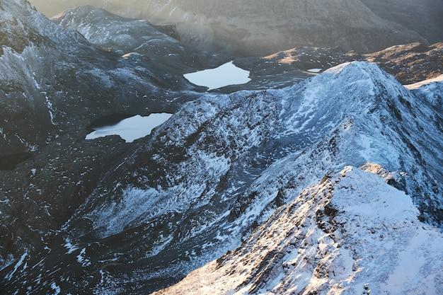 昼間の池の近くの雪に覆われた山の空中ショット 無料写真