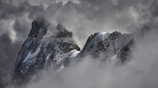 Волшебная съемка красивого снежного горного пика покрытого облаками. Бесплатные Фотографии