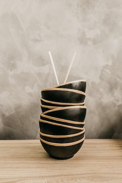 箸を上に重ねて積み上げた黒いフードボウルの垂直ショット 無料写真