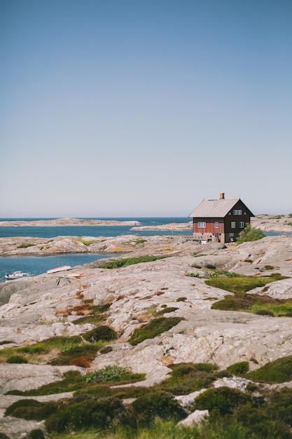 晴れた日に青空の下で海の近くの海岸に孤立した赤い木造住宅 無料写真
