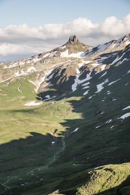 Вертикальный выстрел из травянистых холмов возле снежной горы с облачным небом Бесплатные Фотографии