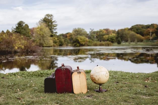 ぼやけた水でデスクグローブの近くの芝生のフィールド上の古いスーツケースのクローズアップショット 無料写真