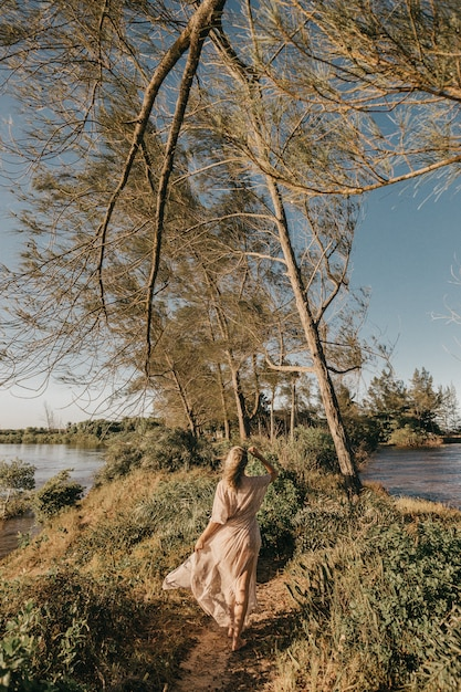 Женщина в белом платье гуляет босиком по маленькому травянистому участку в окружении воды Бесплатные Фотографии