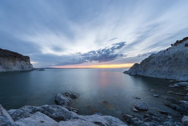 両側に雪に覆われた丘と美しい夕日のシーンの息をのむような海のショット 無料写真