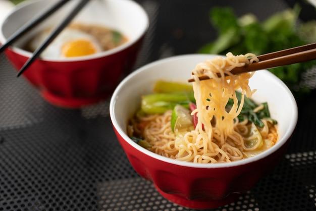 背景をぼかした写真とスープの近くの麺と箸のショットを閉じる 無料写真