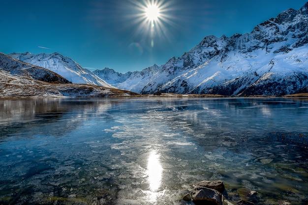 晴れた日の間に雪山に囲まれた美しい凍った湖の息をのむようなショット 無料写真