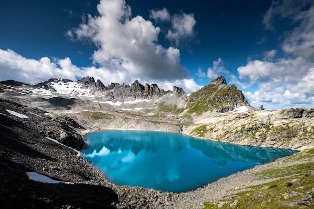 Горизонтальный снимок водоема в окружении скалистых гор под красивым облачным небом Бесплатные Фотографии