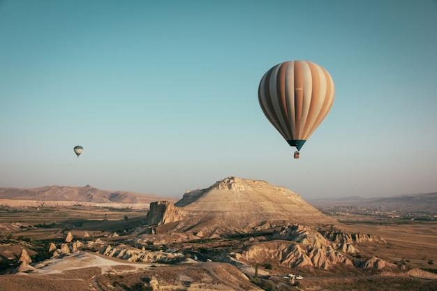 Длинный выстрел из разноцветных воздушных шаров, плавающих над горами Бесплатные Фотографии