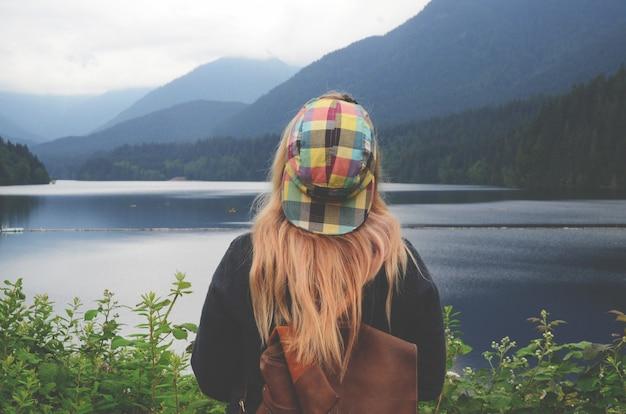 Горизонтальная съемка белокурой женщины с красочной крышкой смотря водоем Бесплатные Фотографии