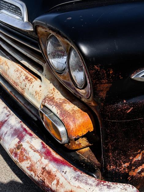 古いさびた黒い自動車のヘッドライトとバンパーの垂直 無料写真