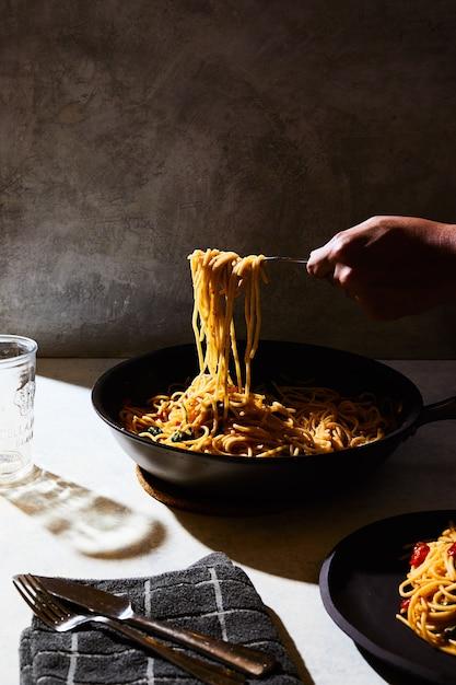 白いテーブルの黒い鍋からスパゲッティを手に入れる人 無料写真