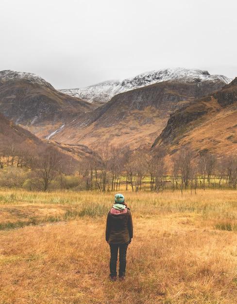 山の下のフィールドの中央に立っている帽子とジャケットの女性の垂直ショット 無料写真