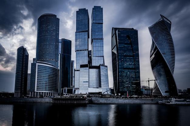 Низкий угол выстрела серых небоскребов перед рекой под темным облачным небом Бесплатные Фотографии