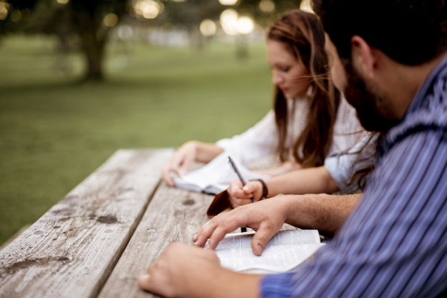 Крупным планом выстрел из людей, сидящих в парке и читающих библию Бесплатные Фотографии