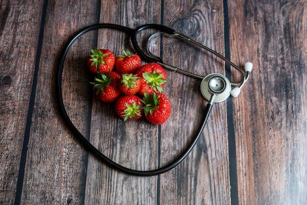 Стетоскоп с клубникой и черный виноград без косточек на вершине деревянный стол. медицина и здравоохранение концептуальные. Бесплатные Фотографии