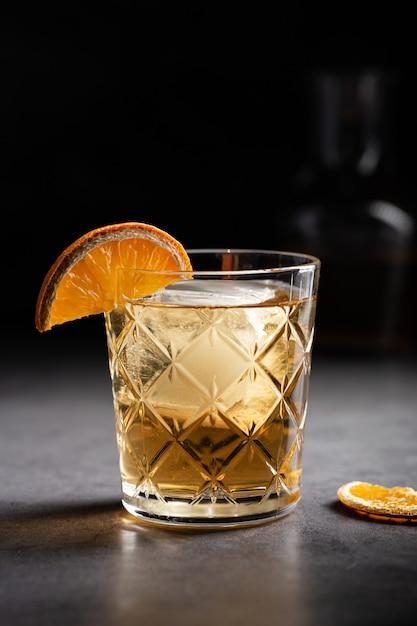 Вертикальный выстрел из стакана виски, украшенного ломтиком сушеного апельсина Бесплатные Фотографии