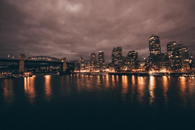 Красивый снимок города и реки ночью Бесплатные Фотографии