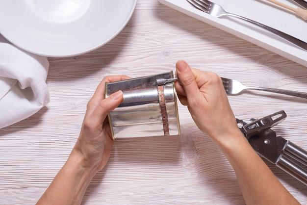 Женщина руки открывая консервную банку с солониной, вид сверху кухонный стол Premium Фотографии