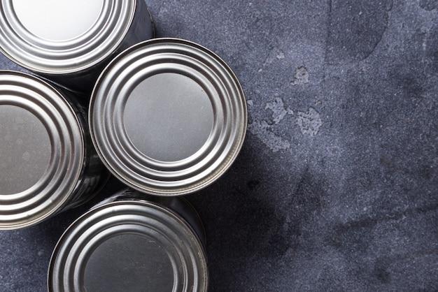 Набор металлических консервных банок на сером темном столе, копия пространства Premium Фотографии