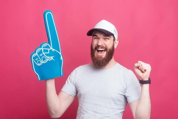 ファンの泡の手袋でさして興奮して若い幸せな男 Premium写真