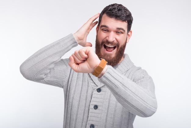 Молодой бородатый человек боится, что он опоздал, он смотрит на свои умные часы. Premium Фотографии