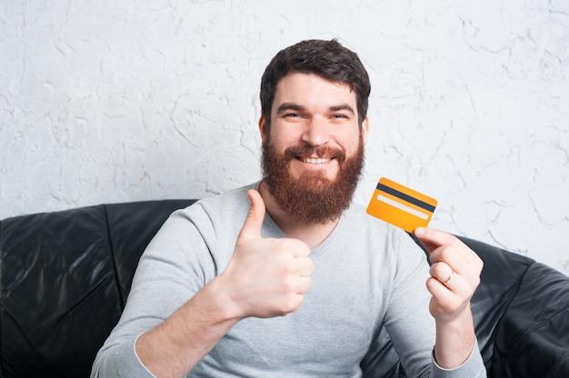 親指を現して、クレジットカードを持っている笑顔幸せな男 Premium写真