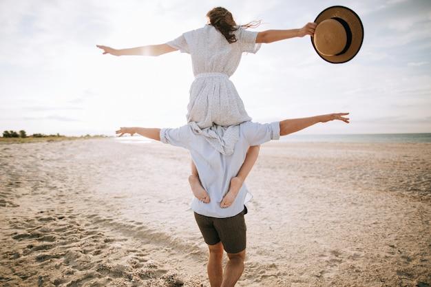 Счастливая пара. молодая женщина на плечи мужа на пляже. концепция летних каникул Premium Фотографии