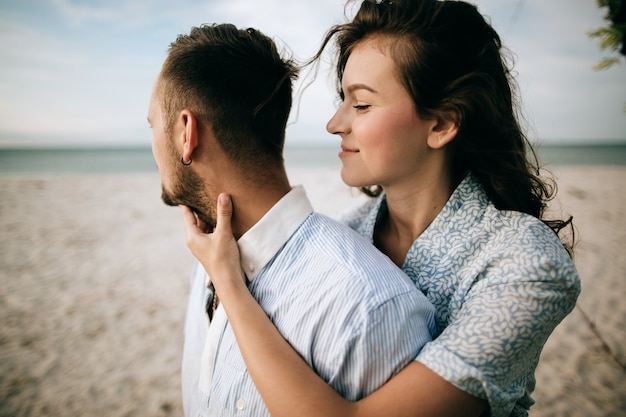 Любить молодая пара обниматься и целоваться на берегу моря. концепция любви Premium Фотографии