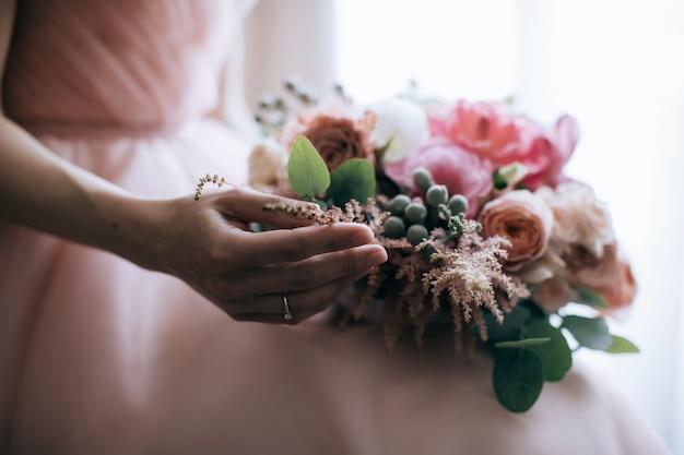 Невеста держит в руках красивый розовый букет Premium Фотографии