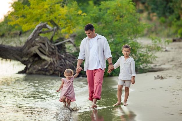 父の日。幸せな日焼けした男が彼の子供たちと娘と息子と一緒に川岸に沿って歩きます。 Premium写真