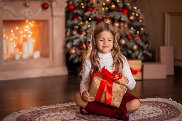 Счастливая девушка с новогодним подарком в руках на фоне камина и елки в огнях Premium Фотографии