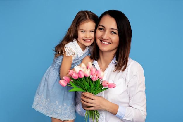 幸せな家族の肖像画。白い歯の笑顔の母と娘が手にピンクのチューリップの花束を握る Premium写真