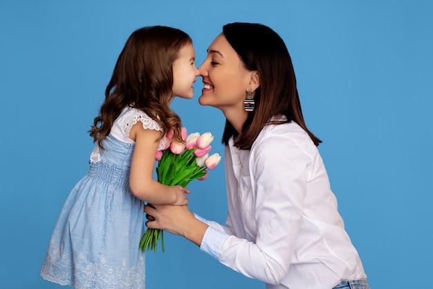 幸せな家族の肖像画。ママと娘はお互いを見ているとピンクのチューリップの花束を持っています。 Premium写真