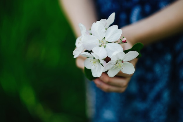 Букет из весенних цветов в руках девушки. цветущая яблоня в парке весной. мягкий фокус. крупный план. Premium Фотографии