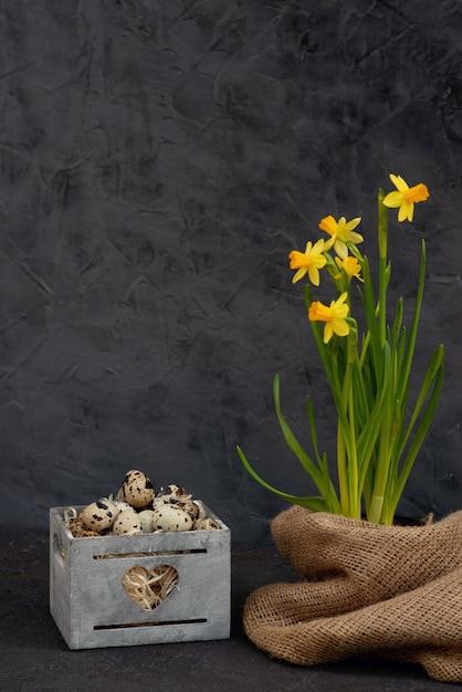 水仙の黄麻布の新鮮な花と木製のバスケットに卵の装飾 Premium写真