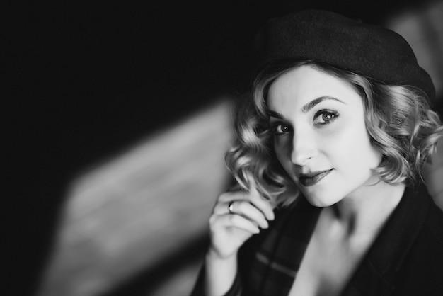 ベレー帽の美しいブロンドの女の子は、レトロなスタイルの黒と白のカメラを見てください。 Premium写真