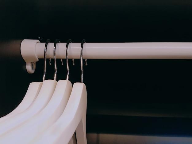 ワードローブの中のラックに掛かっている白い布ハンガーのグループ Premium写真