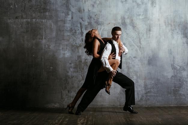黒のドレスとタンゴを踊る大人の男の若い女性。 Premium写真