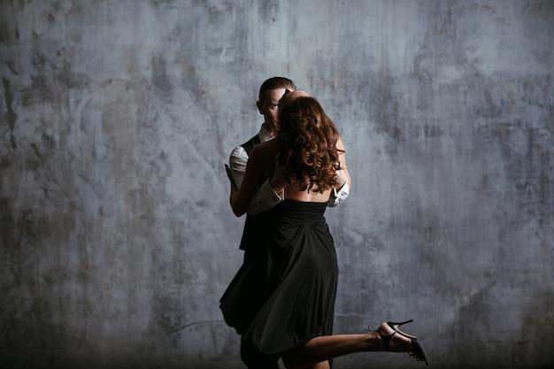 Молодая женщина в черном платье и мужчина танцуют танго Premium Фотографии