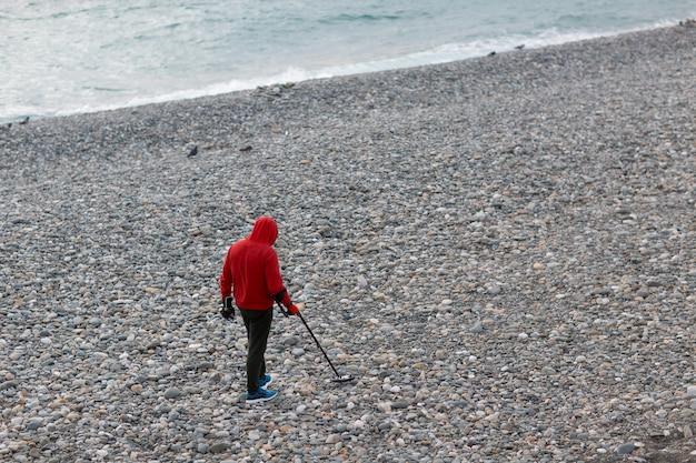 金属探知機を持つ男がビーチでコインやジュエリーを探しています Premium写真