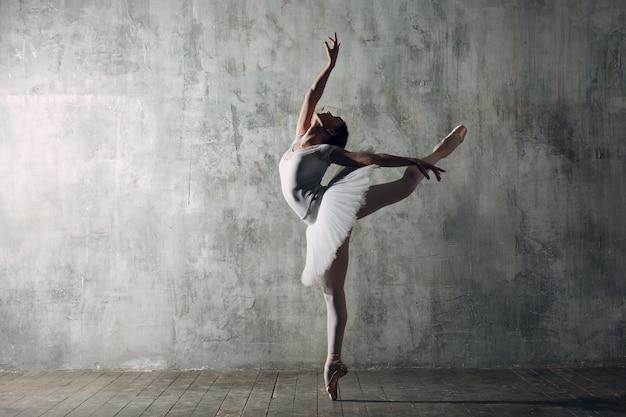 バレリーナの女性。プロの衣装、トウシューズ、白いチュチュに身を包んだ若い美しい女性バレエダンサー。 Premium写真