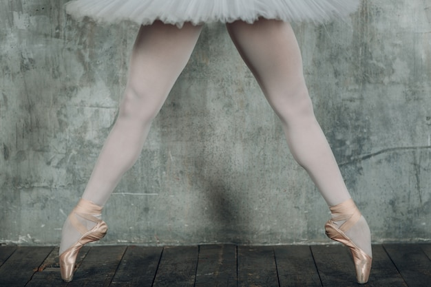 バレリーナ美脚。プロの服、トウシューズ、白いチュチュに身を包んだ若い美しい女性バレエダンサー。 Premium写真