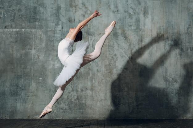 ジャンプバレリーナ。プロの服、トウシューズ、白いチュチュに身を包んだ若い美しい女性バレエダンサー。 Premium写真