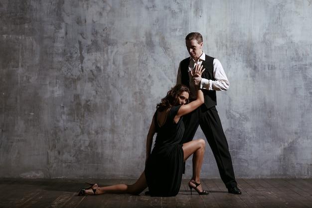 黒のドレスと男の若いきれいな女性ダンスタンゴ Premium写真