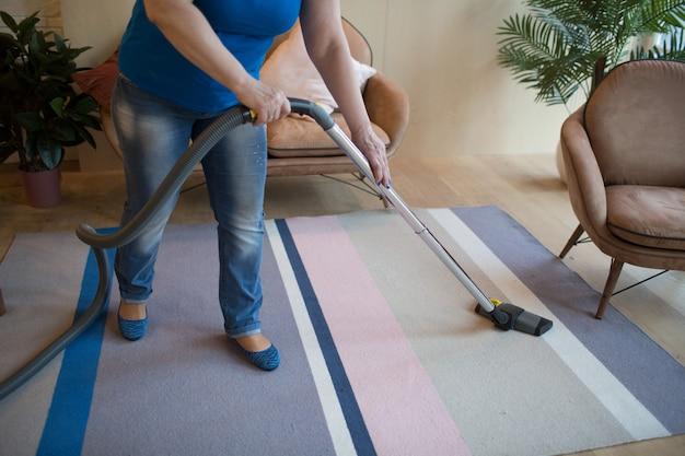 自宅のカーペットを掃除機の女性 Premium写真